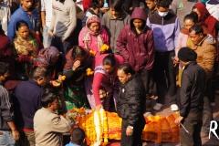Menschen zirkulieren um den Toten, legen ihm frische Blumengirlanden auf den Körper