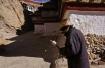 Pilger mit stetig drehender Gebetsmühle in seiner Hand, unterwegs auf dem Kora, der rituellen Umrundung des Kumbum Chörten