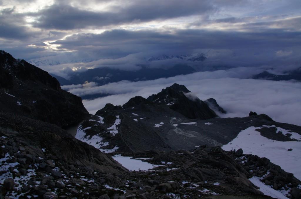 Stimmungsvolle Aussicht ins Tal. Auf der nördlichen Seitenmoräne des kleinen Glacier d'Orny führte uns diesen Tags in dichtem Nebel der Weg zur Hütte. Der Hüttenweg ist wunderschön und flankt entlang der steilen Grashänge weit oberhalb der Combe d'Orny Richtung ESE. Rechts führt der ehemals grosse Gletscherabbruch tief in die Vallon d'Arpette de Saleina. In Richtung der Kamera wäre bei wolkenloser Sicht direkt der Grand Combin ersichtlich.