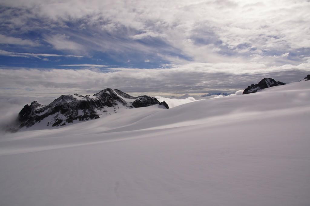 Blick zurück über das immer noch sehr gut zugeschneite Plateau du Trient. In direkter Linie im Fels befindet sich die Cabane du Trient.